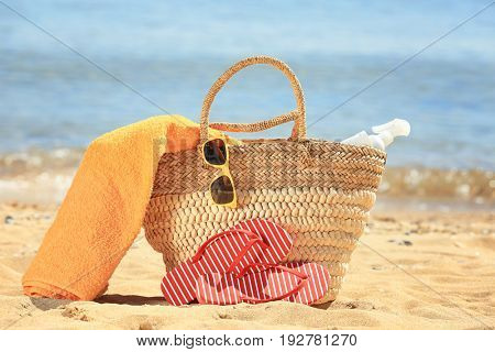 Beach bag and accessories on sand at sea shore. Vacation concept