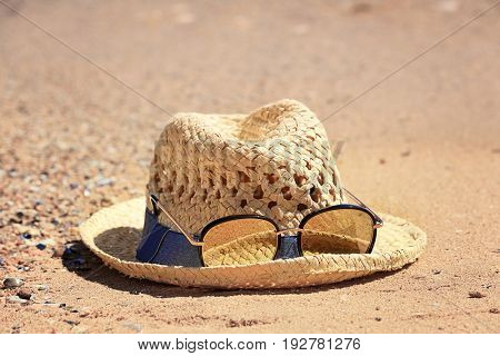 Hat and sunglasses on sand at sea shore. Vacation concept