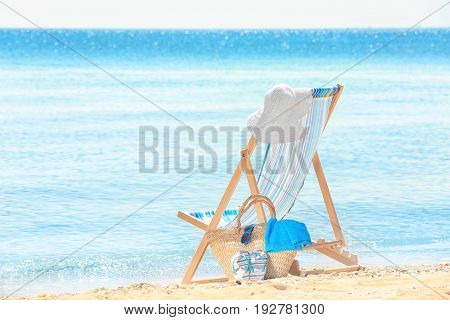 Comfortable beach chair and accessories at sea shore. Vacation concept
