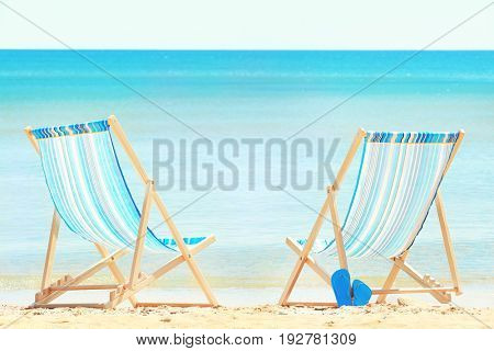 Pair of beach chairs at sea shore. Vacation concept