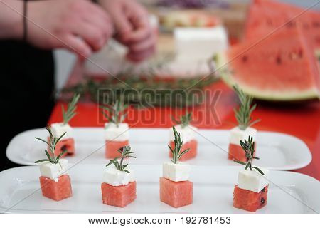 preparing watermelon and feta cheese cubes with rosemary. authentic greek cuisine with selective focus.