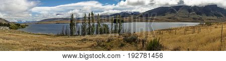 Middle Earth New Zealand - March 14 2017: Panorama shot of Lake Clearwater with dry wasteland in front and the mountains in the back. All under blue cloudy sky.
