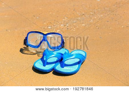 Flip-flops and snorkel mask on sand at sea shore. Vacation concept