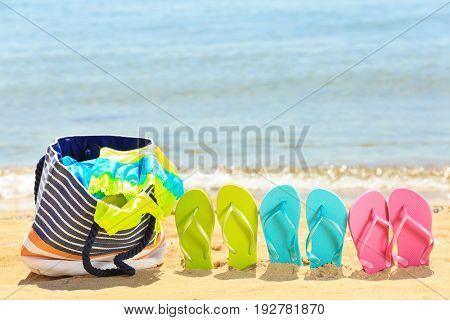 Bag and flip-flops on sand at sea shore. Vacation concept
