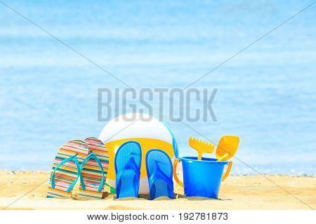 Colorful beach accessories on sand at sea shore. Vacation concept