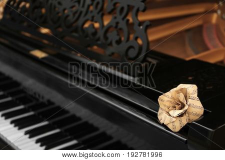 Rose made of music notes on black piano