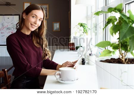 Concentrated At Work. Confident Young Woman In Smart Casual Wear Working On Laptop While Sitting Nea