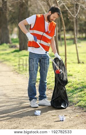 Young volunteer picking up litter in park