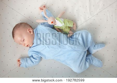 Cute little baby with toy sleeping on bed at home
