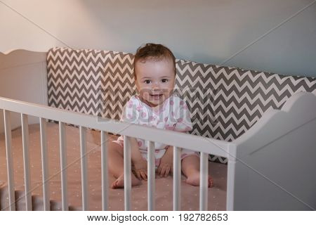 Cute little baby sitting in cradle at home. Sleep disorders concept
