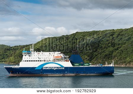 Picton New Zealand - March 12 2017: Bluebridge ferry leaves Picton port under blue and cloudy skies. Green forest on mountains in back.