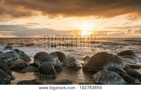 Sun setting over the Pacific ocean and worn rocks from Ke'e Beach on north of Kauai, Hawaii