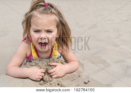 Little girl lying on the sand on the beach screaming mouth wide open, close-up