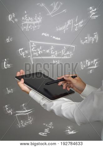 Man scientist or student holding tablet PC and working with various high school maths and science formulas.