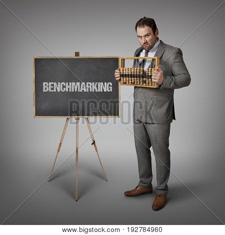 Benchmarking text on blackboard with businessman and abacus
