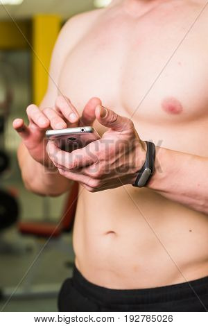 Close-up of Sportive Man After Workout Session Checks Fitness Results Smartphone. Adult Guy Wearing Sport Tracker Wristband Arm. Training hard inside gym.