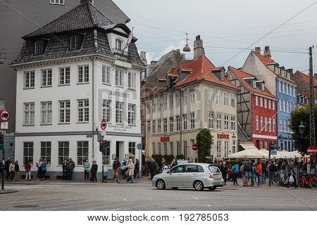 Copenhagen Denmark - July 29 2015: Busy street with traditional colorful houses in Nyhaven district of Copenhagen Denmark.