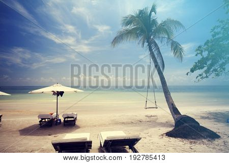 Tropical beach background with palm trees, blue sky and lounge chairs with umbrellas. Vintage effect.