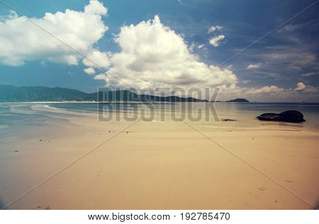 Tropical beach background with white sand and cloudy sky in the sunset. Vintage effect
