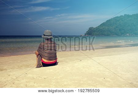 Young woman with hat and scarf relaxing on a beautiful tropical beach