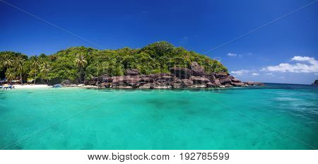 Small remote tropical island with beautiful blue ocean and palm trees