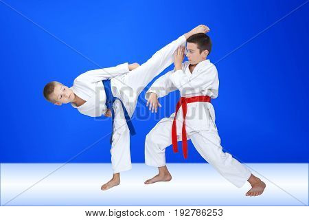 Boys in karategi are training a circular kick and block
