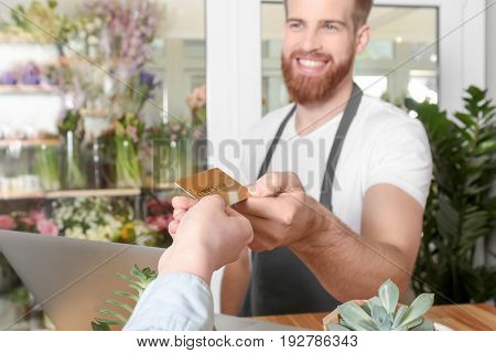 Young handsome florist receiving discount card from regular customer in flower shop