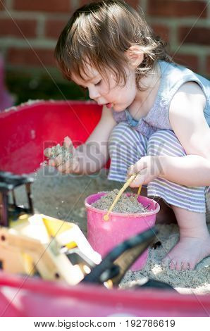 An adorable little girl playing in a sandbox