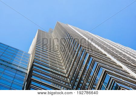 Perspective and underside angle view to textured background of contemporary glass building skyscrapers