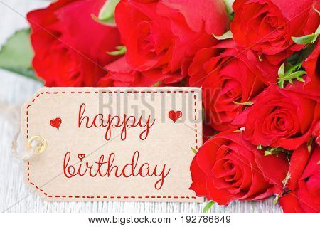 birthday card red roses and a label with text happy birthday closeup