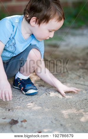 An adorable little boy playing in a sandbox