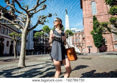 Young female tourist walking with photo camera near the Pauls church in the old town of Frankfurt