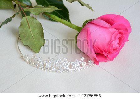 Bridal tiara and pink rose on light background