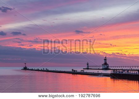 The setting sun paints the sky above Lake Michigan in glorious color and silhouettes the lighthouses and sightseers on the North and South Pier at St. Joseph Michigan.