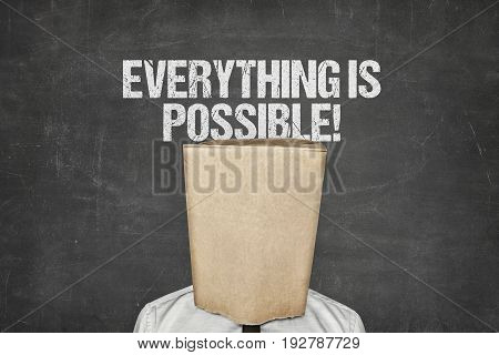 Businessman wearing paperbag in head under everything is possible text on blackboard