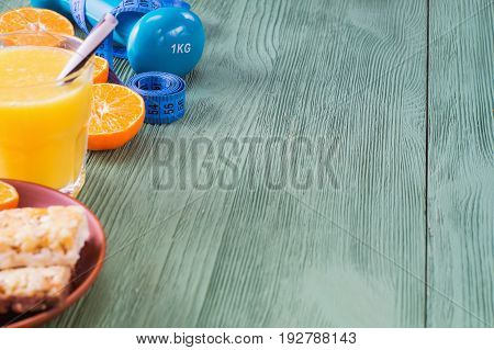 The concept of healthy lifestyle with copy space. Orange juice fruits. cereal bars dumbbell and measuring tape on green wooden table. Cereals and fruits - diet and breakfast