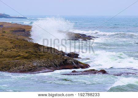 Waves crashing onto the rocky California Coast during high tide
