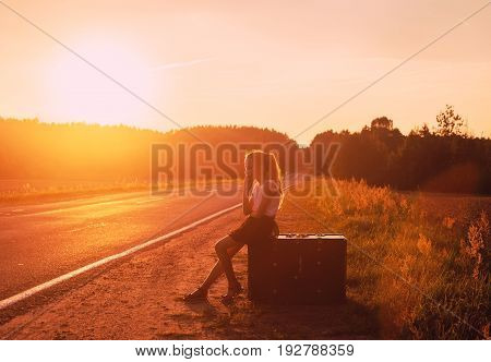 Little Girl relaxing and enjoying road trip. Happy girl sitting at old suitcase on road into the sunset