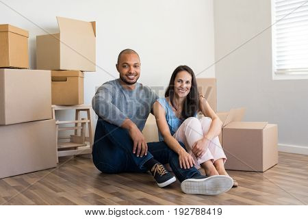 Young multiethnic couple with piles of cardboard boxes after buying a new apartment. African man embrace his smiling girlfriend sitting on floor in their new home. Real estate and loan concept.