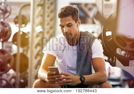 Young handsome man using phone while having exercise break in gym. Guy using smartphone sitting on the bench after the daily training. Latin man listening to music while resting after exercise.