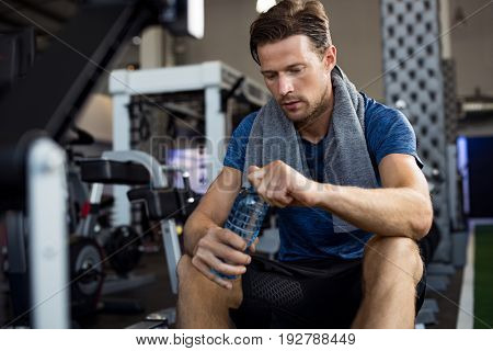 Young man with towel on his shoulders drinking water while sitting at gym. Sweaty guy opening cap of bottle to drink water after workout. Tired man resting after training and holding bottle of water.