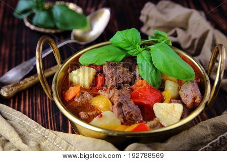 vegetable stew with beef and Basil in a bronze pot