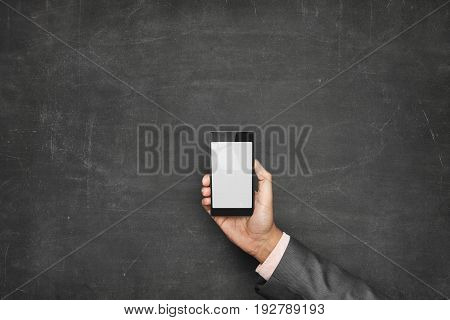 Cropped image of businessman holding smartphone with blank screen against blackboard