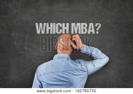 Rear view of confused businessman scratching head while looking at which MBA text on blackboard