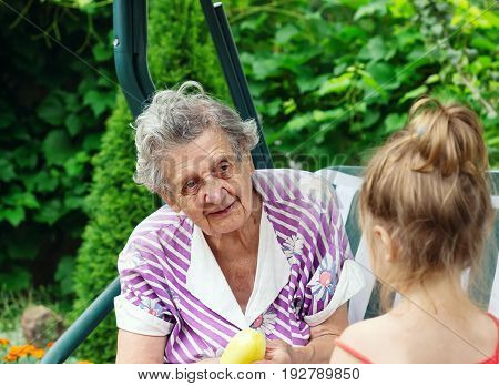 Grandmother with grandchild - senior woman talking at her granddaughter outdoor in nature