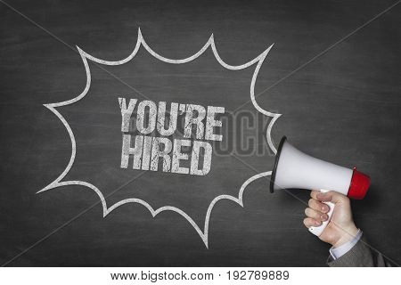 Cropped image of businessman holding megaphone by youre hired text in speech bubble on blackboard