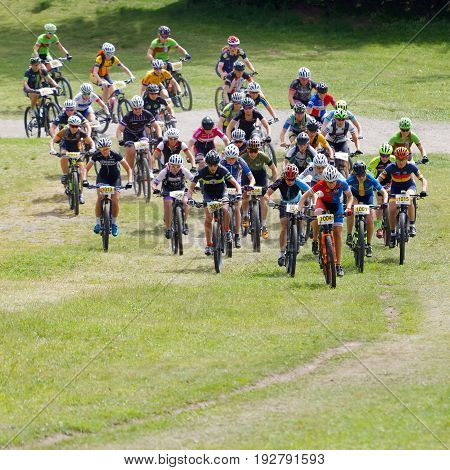 STOCKHOLM SWEDEN - JUNE 11 2017: Large group of fighting mountain bike cyclists i cycling uphill at Lida Loop Mountain bike Race audience in background. June 11 2017 in Stockholm Sweden