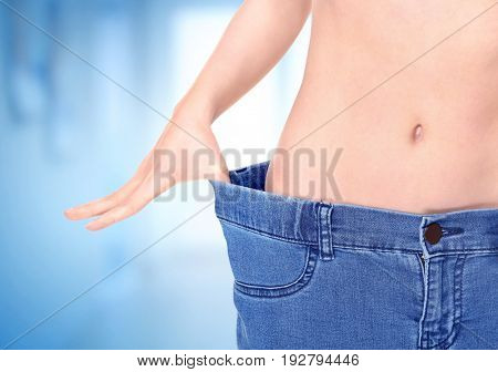 Weight loss concept. Young woman in big size jeans on blurred background