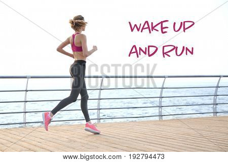 Fitness quotes. Text WAKE UP AND RUN on background. Young woman running on pier