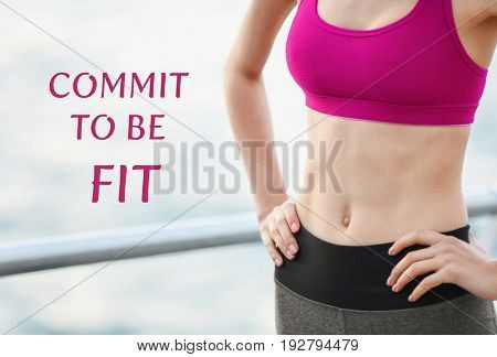Fitness quotes. Text COMMIT TO BE FIT on background. Young woman in sportswear standing on pier